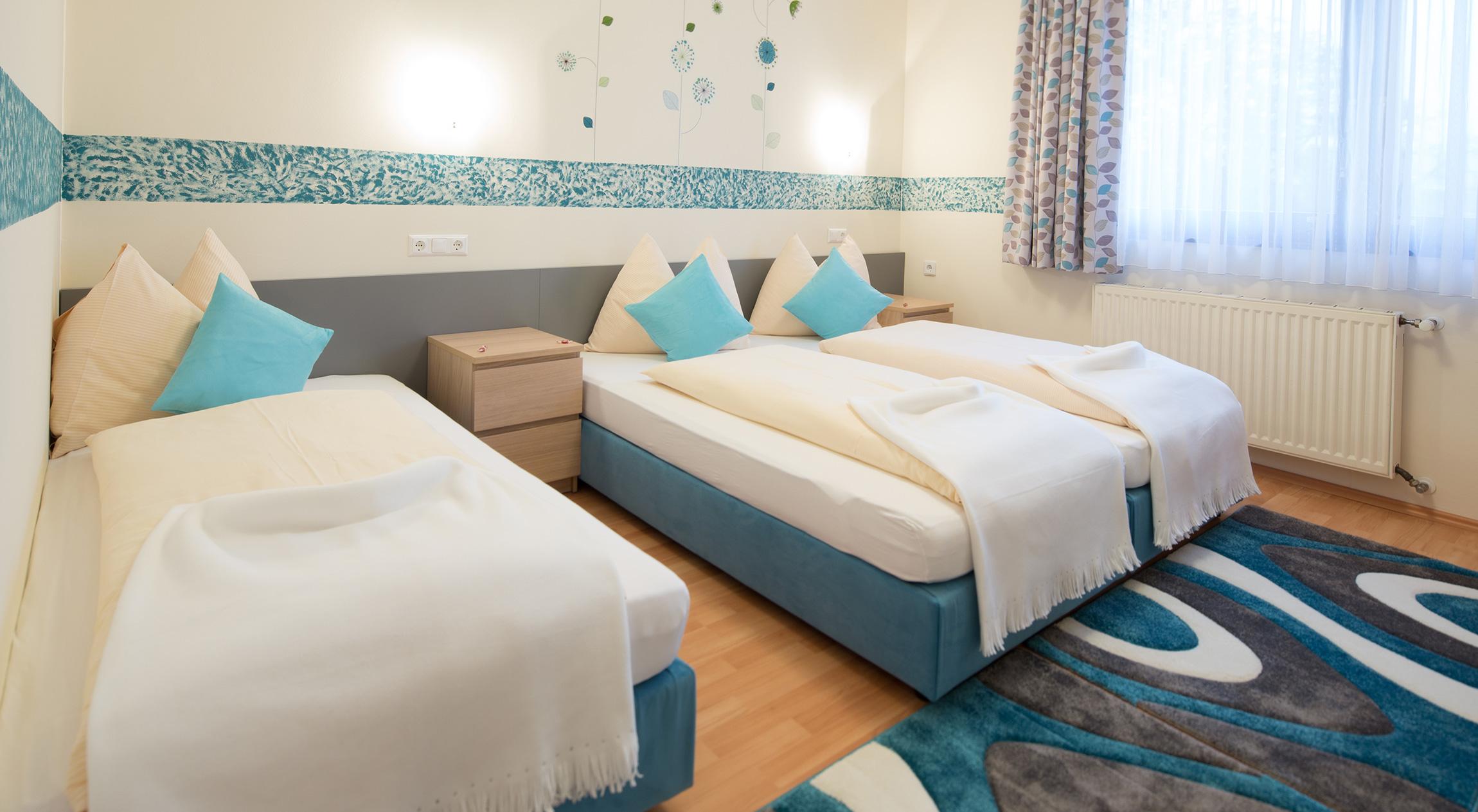 Dreibettzimmer im Hotel Zlami-Holzer in Klagenfurt in der Farbe blau