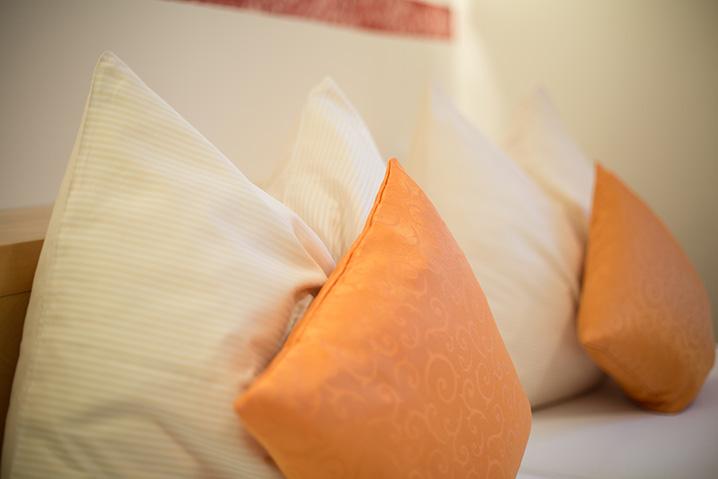 Doppelzimmer im Hotel Zlami-Holzer mit weißen und orangen Pölstern