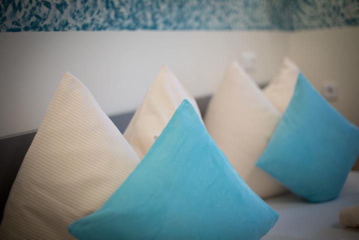 Dreibettzimmer im Hotel Zlami-Holzer mit blauen und weißen Pölstern