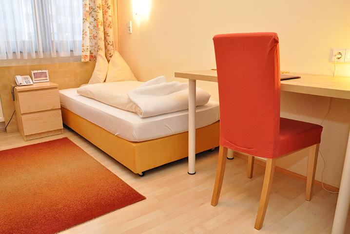 Einbettzimmer im Hotel Zlami-Holzer in der Farbe orange
