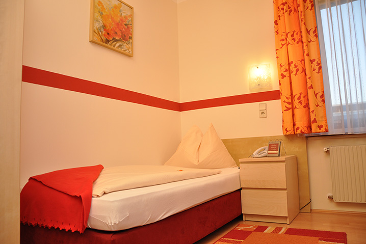 Einbettzimmer im Hotel Zlami-Holzer in der Farbe rot.